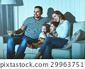 Family watching television at home on sofa 29963751