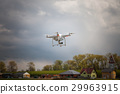 Drone flying over a field next to the village 29963915