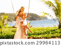 happy family at beach. mother shook child on swing in summer. 29964113