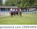 Race horses and jockeys during a race 29964806