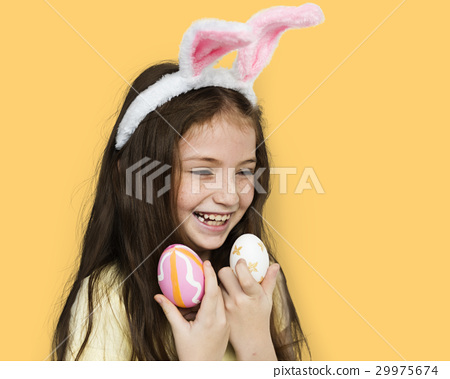 Kid with a bunny hairband holding eggs 29975674