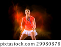 Young woman playing badminton over black 29980878