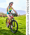 Woman traveling bicycle on green grass in summer 29982154