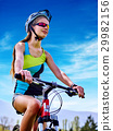 Woman traveling bicycle on green grass in summer 29982156