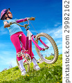 Woman traveling bicycle on green grass in summer 29982162