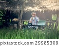Old man sitting at a desk on a outdoor 29985309