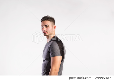 Young handsome fitness man in gray t-shirt, studio 29995487