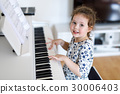 Beautiful little kid girl playing piano in living 30006403