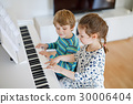 Two little kids girl and boy playing piano in 30006404