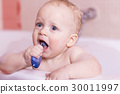 Funny baby boy brushes his teeth. Blue-eyed 30011997