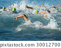 Group people in wetsuit swimming at triathlon 30012700
