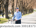 Senior man in blue checked shirt with bicycle in 30018373
