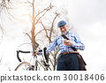Senior man with smartphone and bicycle in town. 30018406