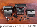 Typewriters, Stamps and Pens on Wood Desk 30034191