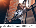 Young girl with a saxophone - outdoor  30035213