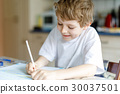 Happy school kid boy at home making homework 30037501