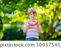 little preschool kid boy eating watermelon in 30037545