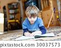 Happy school kid boy at home making homework 30037573