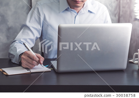Businessman writing some data in notebook  30038758
