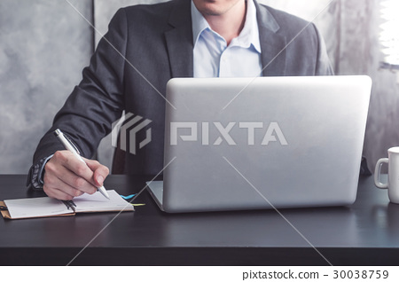 Businessman writing some data in notebook  30038759