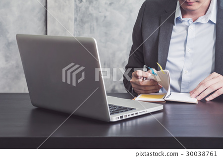 Businessman reading notebook on the desk 30038761