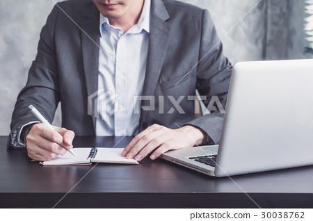 Businessman writing some data in notebook  30038762