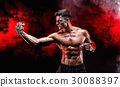Serious muscular fighter doing the punch with the 30088397