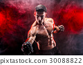 Serious muscular fighter doing the punch with the 30088822