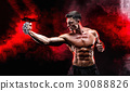Serious muscular fighter doing the punch with the 30088826