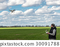 man operating of flying drone quadrocopter at the 30091788
