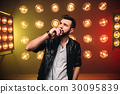Brutal bearded singer with microphone on the stage 30095839