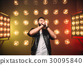 Brutal bearded singer with microphone on the stage 30095840