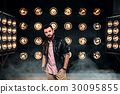 Bearded singer on stage with decorations of lights 30095855