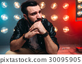 Bearded singer on stage with decorations of lights 30095905