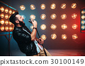 Brutal bearded singer with microphone on the stage 30100149