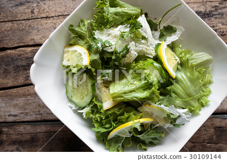 Fresh Salad In White Bowl On Wooden Background Stock Photo