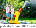 Two little kids boys playing with a garden hose 30117544