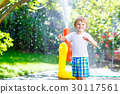little kid boy playing with a garden hose water 30117561
