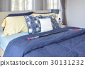 stylish bedroom with blue patterned pillows on bed 30131232