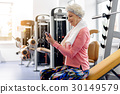Smiling grandmother hearing song in fitness center 30149579