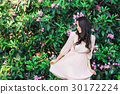 Portrait of young beautiful woman posing among 30172224