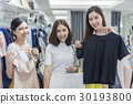 A group of women are trying clothes in the store. 30193800