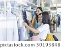 A group of women are choosing clothes in the shopping mall. 30193848