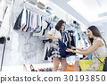 two ladies are choosing new skirt in clothes store. 30193850