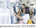 Beautiful ladies discussing new clothes in shopping mall. 30193865