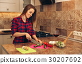 Portrait of smiling young housewife in modern 30207692
