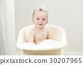 Smiling boy sitting in bath covered in foam 30207965