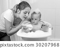 Portrait of mother playing with baby in bath 30207968