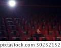 Young pensive man watching movie in theater 30232152