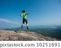 jumping on rocky mountain peak  30251691